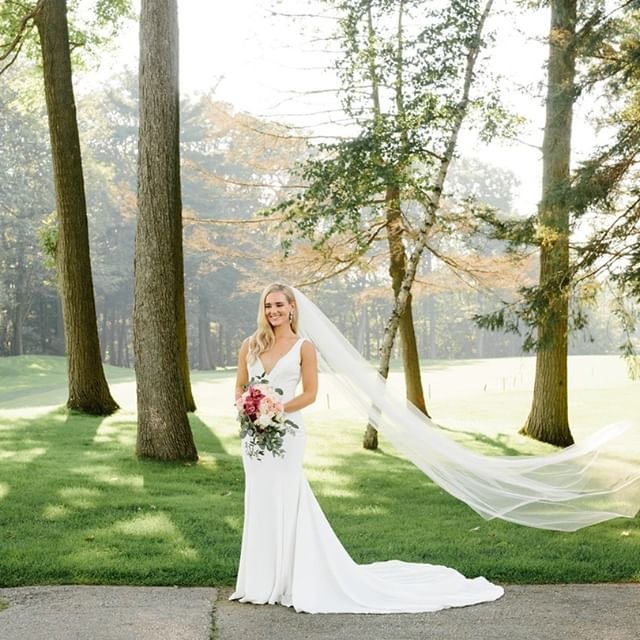 bride standing beside some trees