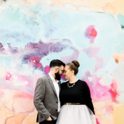 Happy couple in front of decorated wall